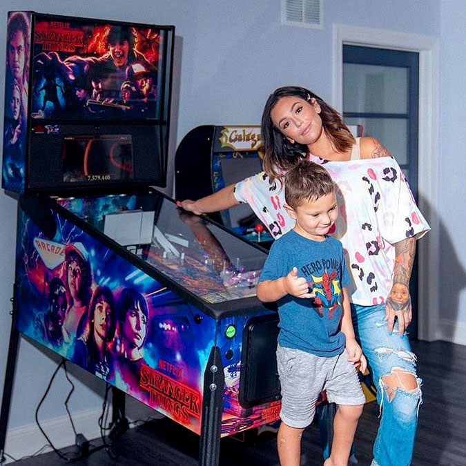 Jwoww playing Stern's Stranger Things pinball with her son